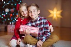 Deux enfants heureux dans la soirée du Nouveau an avec des présents s'approchent de la nouvelle année T Photos stock