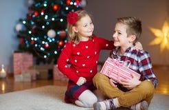 Deux enfants heureux dans la soirée du Nouveau an avec des présents s'approchent de la nouvelle année T Image stock