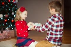 Deux enfants heureux dans la soirée du Nouveau an avec des présents s'approchent de la nouvelle année T Image libre de droits