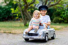 Deux enfants heureux jouant avec la grande vieille voiture de jouet en été font du jardinage, dehors Badinez le garçon conduisant image libre de droits