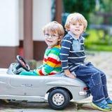Deux enfants heureux jouant avec la grande vieille voiture de jouet en été font du jardinage, OU Images libres de droits