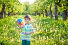 Deux enfants heureux jouant dans le jardin avec le moulin à vent Photographie stock libre de droits
