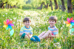 Deux enfants heureux jouant dans le jardin avec le moulin à vent Image libre de droits