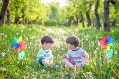 Deux enfants heureux jouant dans le jardin avec le moulin à vent Photos libres de droits