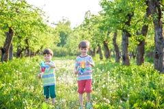 Deux enfants heureux jouant dans le jardin avec le moulin à vent Images stock