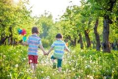 Deux enfants heureux jouant dans le jardin avec le moulin à vent Images libres de droits
