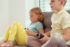 Deux enfants heureux jouant des jeux vidéo à la maison Photos stock