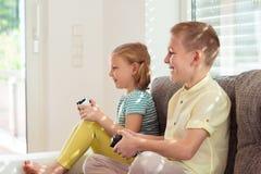Deux enfants heureux jouant des jeux vidéo à la maison Photos libres de droits