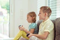 Deux enfants heureux jouant des jeux vidéo à la maison Images libres de droits