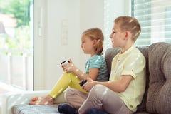 Deux enfants heureux jouant des jeux vidéo à la maison Photographie stock