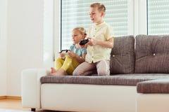 Deux enfants heureux jouant des jeux vidéo à la maison Photo stock
