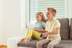 Deux enfants heureux jouant des jeux vidéo à la maison Image libre de droits