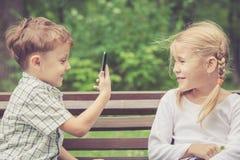 Deux enfants heureux jouant en parc au temps de jour Photo stock