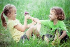 Deux enfants heureux jouant près de l'arbre au temps de jour Images stock