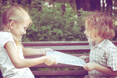 Deux enfants heureux jouant près de l'arbre au temps de jour Photographie stock libre de droits