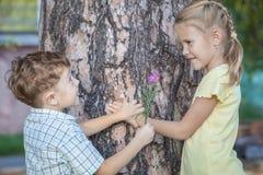 Deux enfants heureux jouant près de l'arbre au temps de jour Photos libres de droits