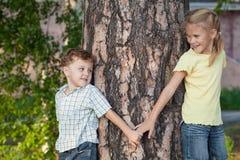 Deux enfants heureux jouant près de l'arbre au temps de jour Images libres de droits