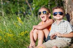 Deux enfants heureux jouant près de l'arbre au temps de jour Photos stock