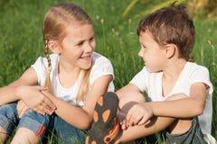 Deux enfants heureux jouant près de l'arbre sur l'herbe au jour Photographie stock libre de droits