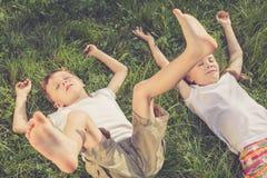 Deux enfants heureux jouant sur l'herbe au temps de jour Images libres de droits