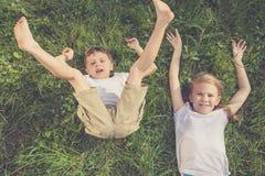 Deux enfants heureux jouant sur l'herbe au temps de jour Photographie stock