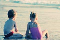 Deux enfants heureux jouant sur la plage Photographie stock libre de droits