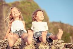Deux enfants heureux jouant sur la plage Image libre de droits