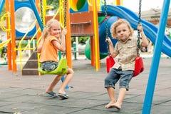 Deux enfants heureux jouant sur le terrain de jeu au temps de jour Photographie stock libre de droits