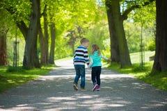Deux enfants heureux marchant en parc Images stock