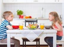Deux enfants heureux prenant le petit déjeuner dans la cuisine Photos stock