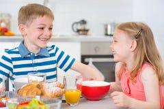 Deux enfants heureux prenant le petit déjeuner dans la cuisine Image stock