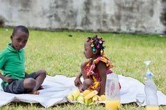Deux enfants heureux s'asseyant dans un jardin pique-niquant images stock