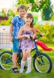 Deux enfants heureux s'asseyant sur la bicyclette image libre de droits