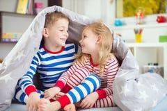 Deux enfants heureux se cachant sous la couverture Images stock