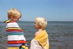 Deux enfants heureux souriant à l'un l'autre sur la plage Photos stock
