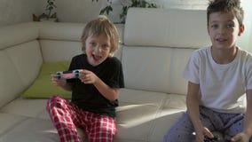 Deux enfants jouant avec émotion des jeux vidéo à la maison au matin ensoleillé clips vidéos