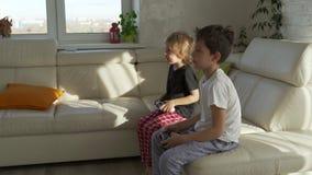 Deux enfants jouant avec émotion des jeux vidéo à la maison au matin ensoleillé banque de vidéos