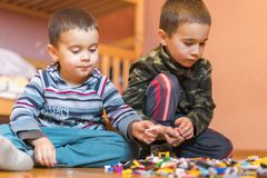 Deux enfants jouant avec un bon nombre de constructeur en plastique coloré de blocs se reposant sur un plancher d'intérieur Jeu d photo stock