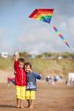 Deux enfants jouant avec un cerf-volant sur la plage Photos stock