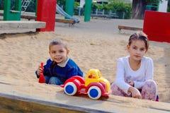 Deux enfants jouant ensemble dans le bac à sable Photos stock