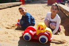 Deux enfants jouant ensemble dans le bac à sable Photographie stock libre de droits