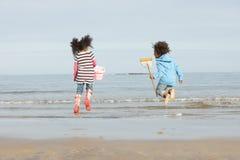 Deux enfants jouant par la plage de l'hiver de Sea On Images libres de droits