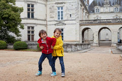 Deux enfants, jouant sous la pluie devant le château de Le Lude Photo libre de droits