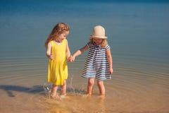 Deux enfants jouant sur la plage dans l'eau Photographie stock