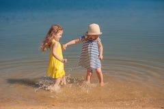 Deux enfants jouant sur la plage dans l'eau Image libre de droits