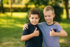 Deux enfants jouent en parc Deux beaux garçons dans le T-shirts et les shorts ont le sourire d'amusement Ils mangent la crème gla Images libres de droits