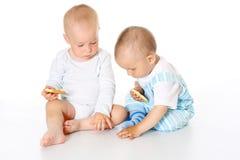 Deux enfants joyeux mignons s'asseyant ensemble sur le fond blanc d'isolement photos stock