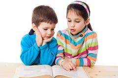 Deux enfants lisant le livre à la table Images stock
