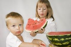 Deux enfants mangent la pastèque photo stock