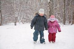 Deux enfants marchant dans la neige Photos libres de droits
